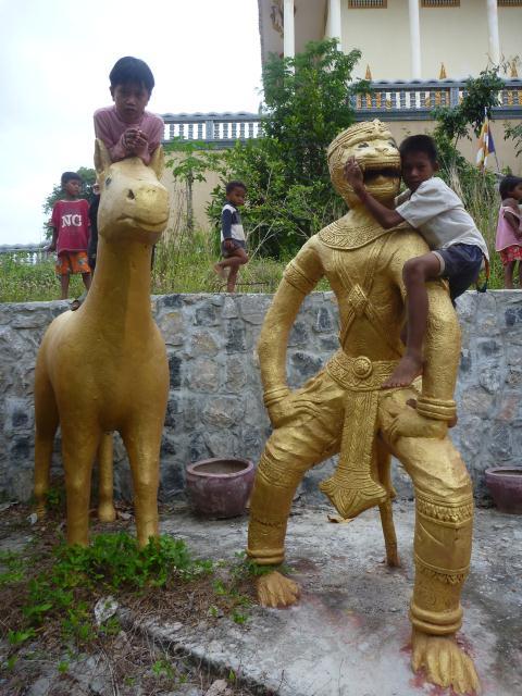 Les enfants s'éclatent avec les statues dorées du temple.
