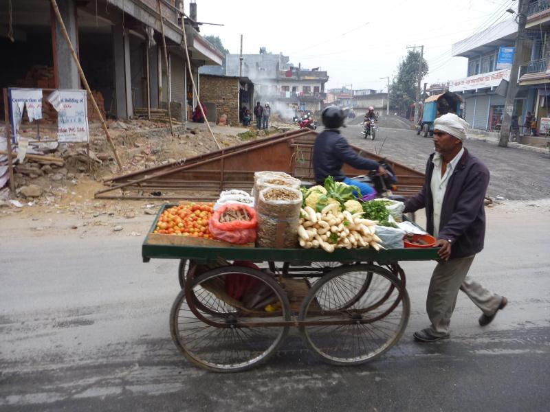 Un marchand ambulant pousse sa charrette pour aller vendre ses légumes un peu plus loin.
