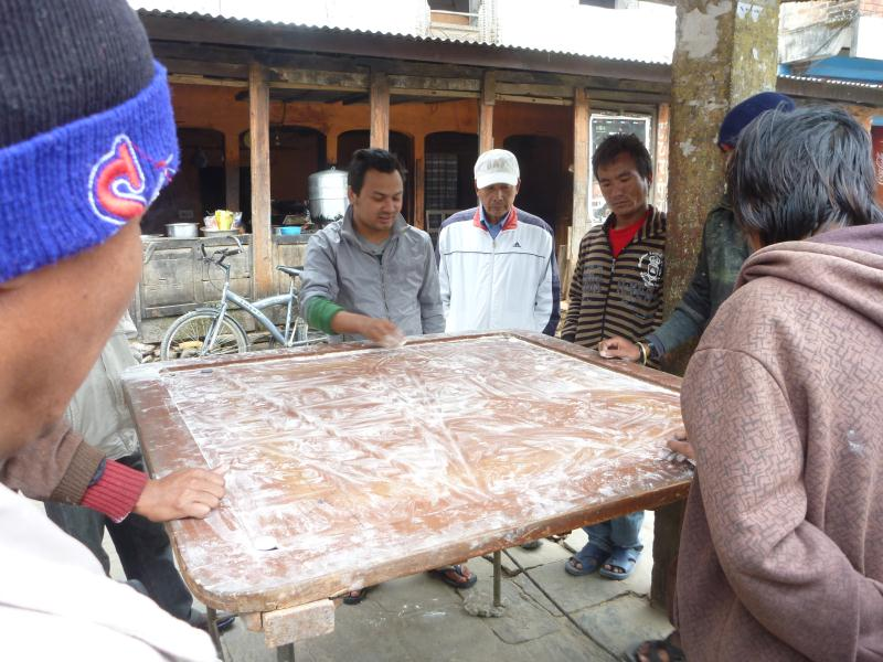 Un jeu très populaire au Népal, ca ressemble à du billard mais ca se joue avec des palais. On tire avec le doigt pour lancer le palais qui en fera rentrer un autre dans un trou d'angle.